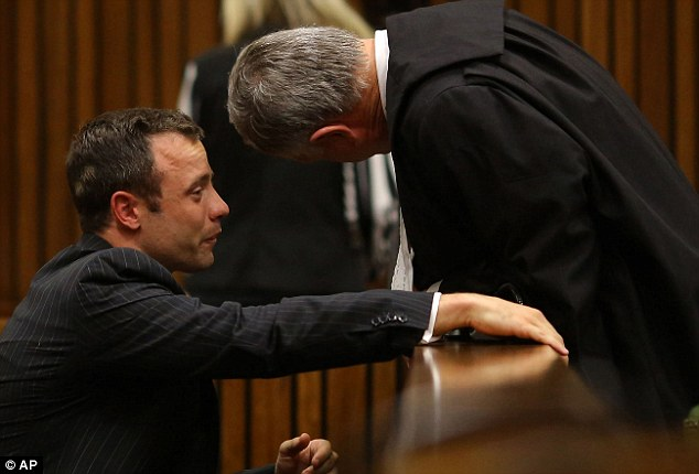 Distraught: A sobbing Oscar Pistorius talks to his lawyer Barry Roux after listening to evidence in his case