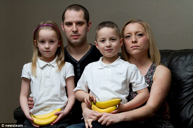 Scare: Jamie and Crystal Roberts with their daughter Georgiana, seven and son Joshua, eight, at their home in Hednesford, Staffordshire. The family found a nest of spiders on bananas they bought from a OneStop Store