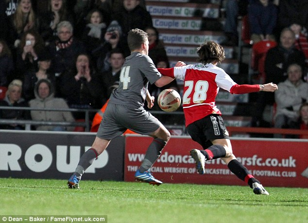 Getting stuck in: Tomlinson (right), pictured here challenging a Rotherham player for the ball, helped attract a crowd of over 5,000 to the game