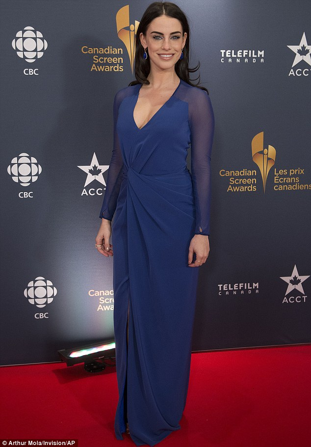 Working the red carpet: Wearing a divinely deep sapphire plunge dress, with sheer long sleeves, the Canadian-born beauty wore her hair in loose curls, with a centre parting, which accentuated the shape of her face