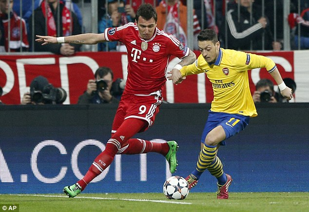 Fully focused: Arsenal midfielder Mesut Ozil (right) tussles with Bayern striker Mario Mandzukic (left)