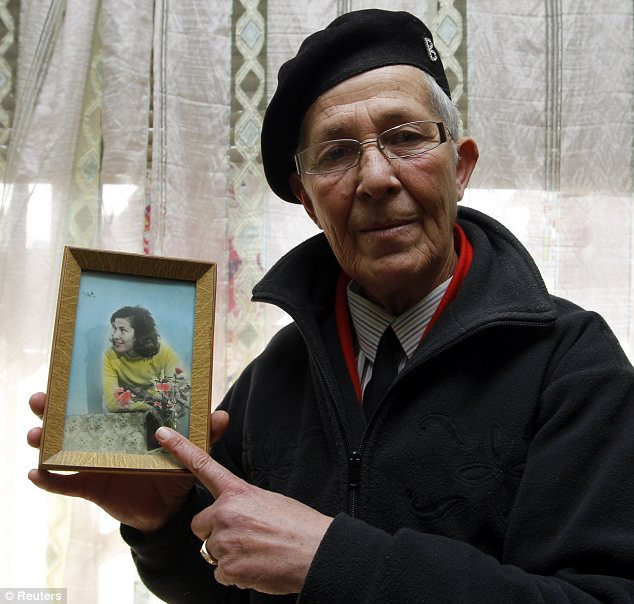Dying breed: Diane Rakipi, pictured with a photo of herself as a young girl, is one of the few remaining Burrneshas in Albania