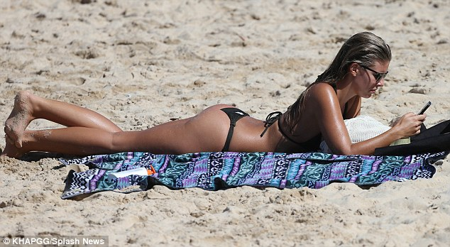 Updating your Instagram? The deeply-tanned young Australian looks at her phone while clad in some skimpy bikini bottoms