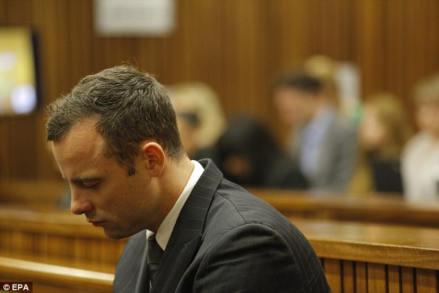 Back for another day: Pistorius sits in the dock as pathologist Gert Saayman prepares to continue his testimony about Reeva Steenkamp's post mortem on day seven of his trial