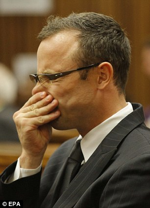 Pistorius rubs his nose as he sits in the dock during day seven of his murder trial