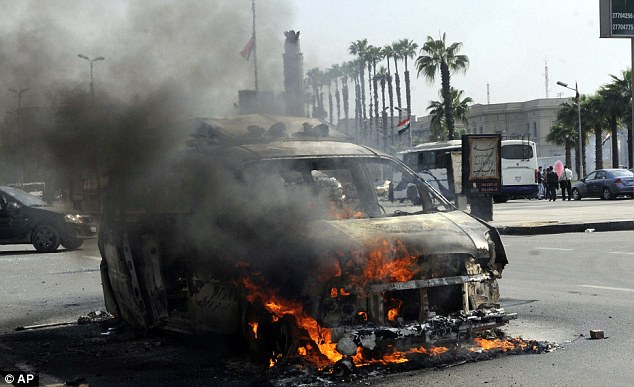 Troubles: Egypt continues to be dogged by protest and political strife - this was a satellite television truck in flames near the Cairo University campus on Sunday