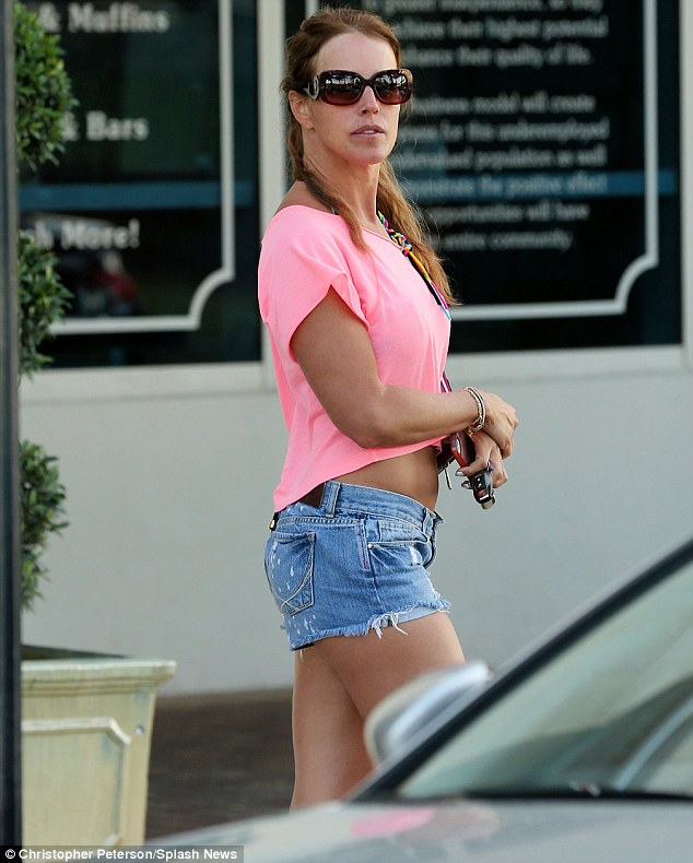 Covered up: The TV personality dashed on a coral blouse and jean shorts to walk outside of the beach