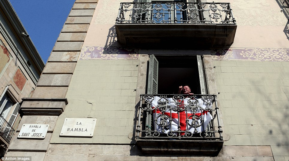 Mission impossible: A City fan hangs a St George's Cross out of his window on La Rambla in preparation
