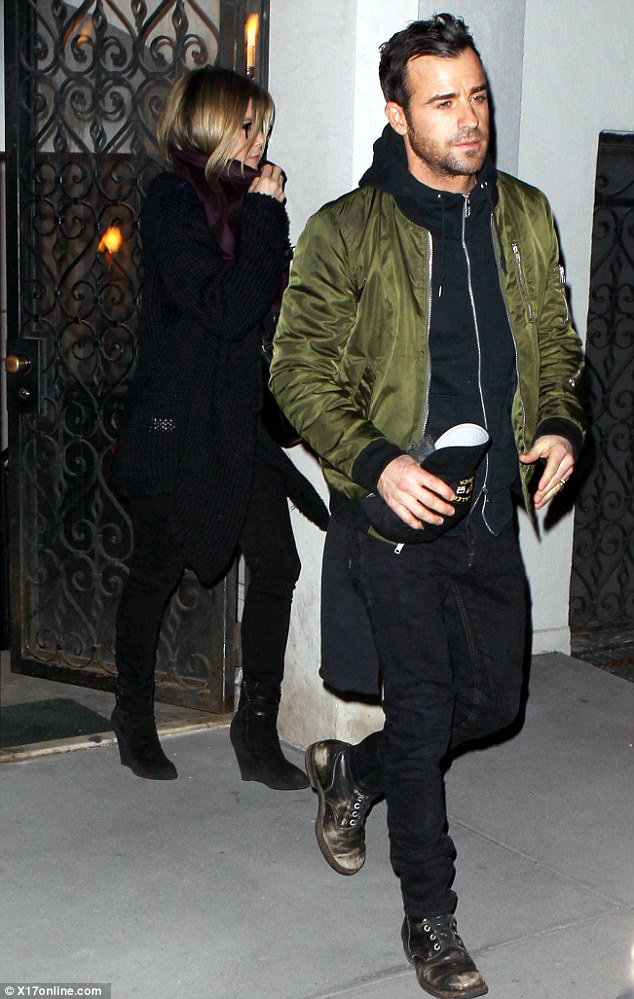 Hat's off to you: Justin opted for a silky green-coloured coat for the evening and carried a baseball cap as he departed the restaurant