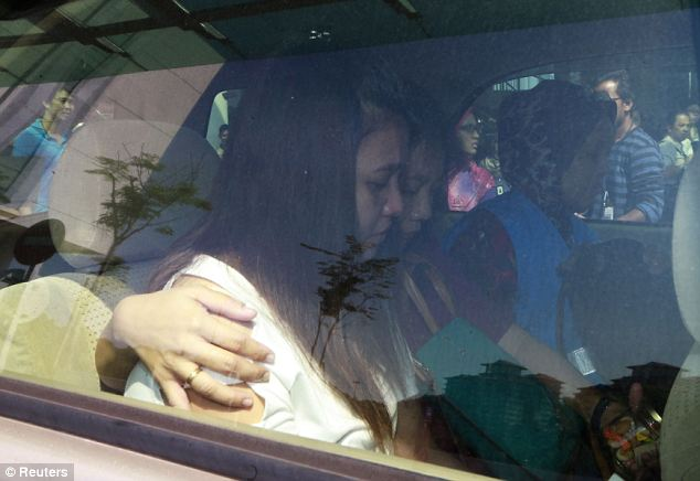 Tough time: More relatives of missing passengers are photographed in a car outside the Kuala Lumpur hotel