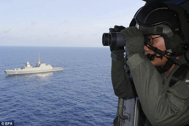The search continues: A helicopter crewman from Singapore's Navy uses binoculars to scour the ocean in the hunt for missing Malaysian Airlines flight MH370, which has vanished without a trace