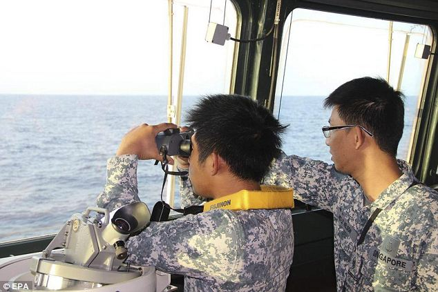 Hunt: Two Singapore Navy sailors look at at the featureless sea during the search in this picture released today