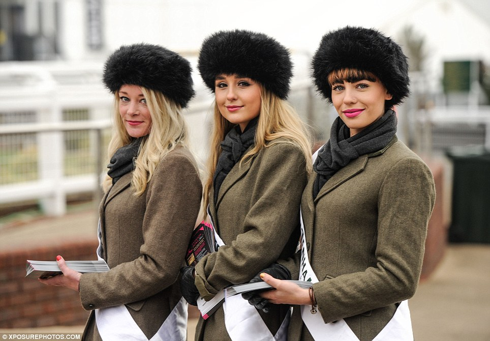 Looking good: The Cheltenham Festival ladies are resplendent in furry cossack hats and chic tweed jackets as they greet racegoers arriving at the course for Ladies Day