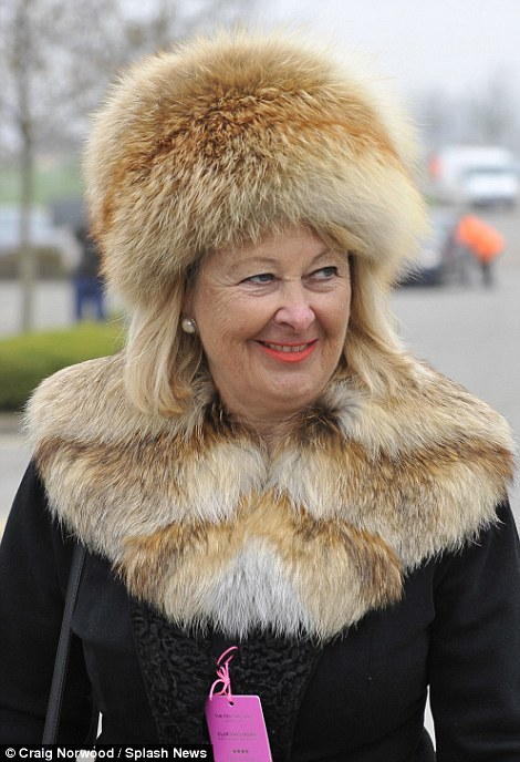 A racegoer in a furry cossack hat arrives for the races