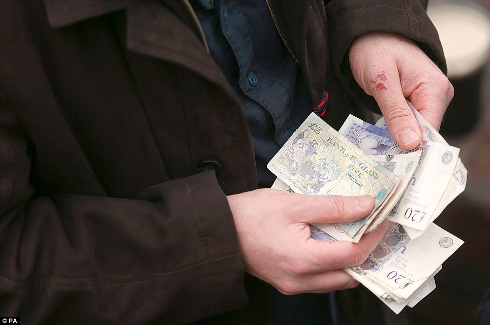 Flashing the cash: A punter counts his money as he decided whether to place a bet on one of today's races, the highlight of which is expected to be the Weatherbys Champion Bumper