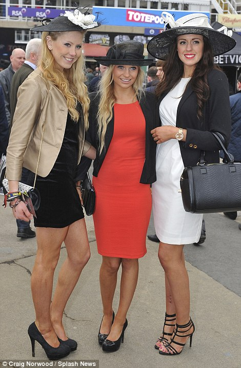 A trio of racegoers dressed in their best