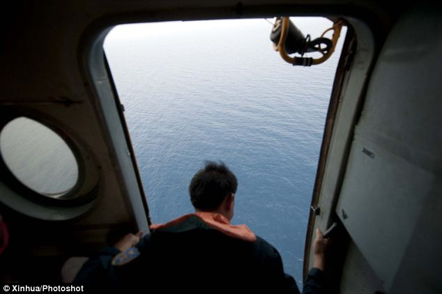 An officer aboard a Vietnamese military helicopter scours the waters in the area where the flight vanished