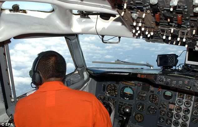 An Indonesian Airforce pilot looks out of a military surveillance airplane over the Malacca straits during a search mission for missing Malaysia Airlines flight MH370, which disappeared on Saturday en-route to Beijing