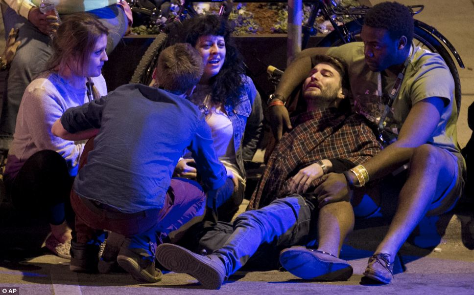 Festival-goers are comforted after being struck by a vehicle on Red River Street in downtown Austin, Texas