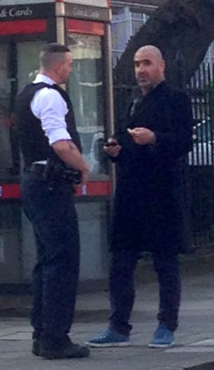 Football legend Eric Cantona is confronted by a police officer in North London yesterday