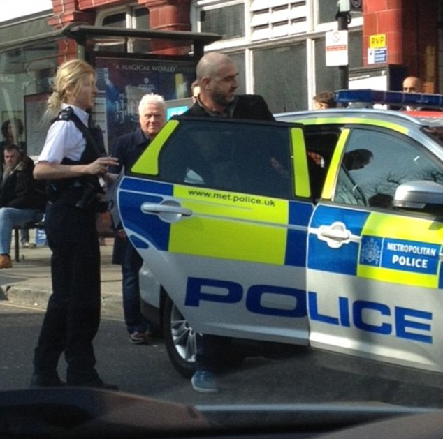 Eric Cantona is ushered into a police car after being arrested for assault in north London