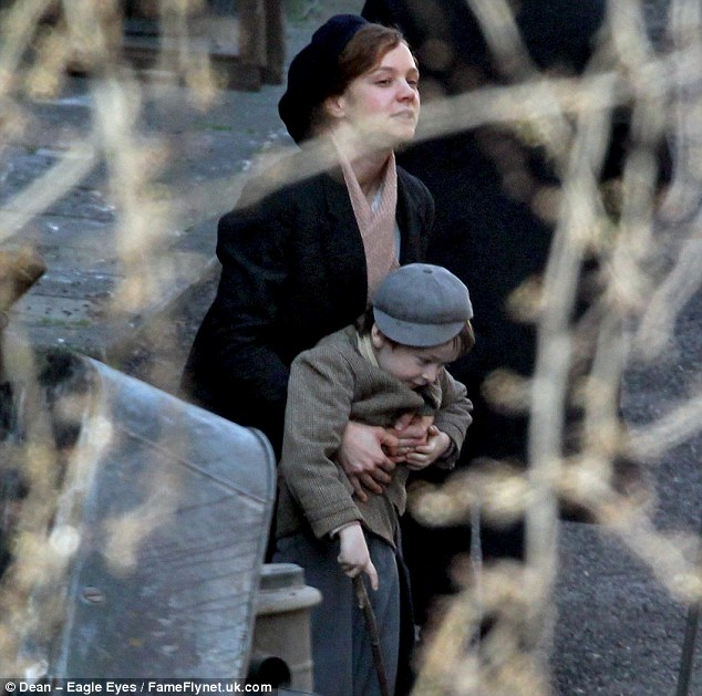 Practising for real life: Carey larks around with her little co star on  set