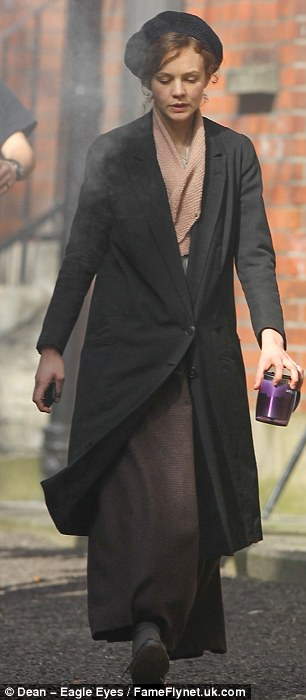 Foot soldier: She looks drab in a cumbersome coat and knitted beret as the walks around on set during a film break sipping coffee from a purple mug