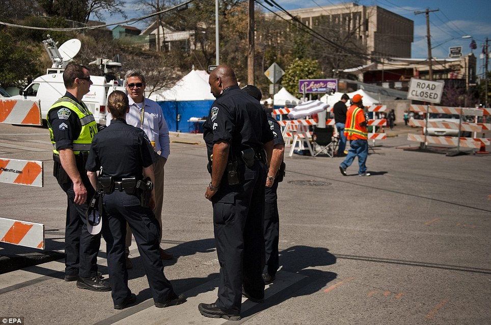 Austin police and investigators talk near the site, which is now clogged with the authorities, and various news outlets covering both the SXSW festival and the crash