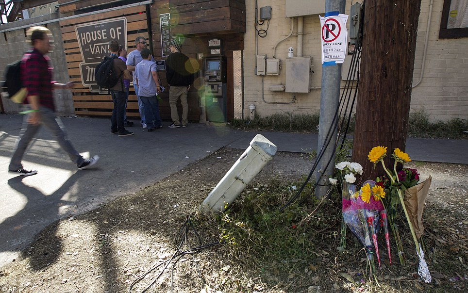 Flowers placed against a utility pole near the scene where 2 people were killed and 23 others injured when a motorist fleeing police drove his car through a crowd of pedestrians near Mohawks
