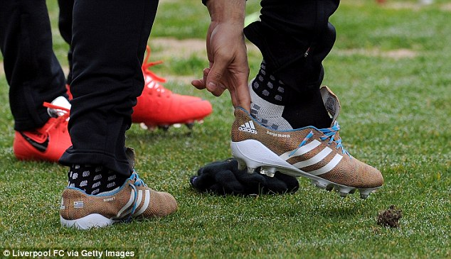 Leading the way: Suarez puts on his new knitted boots before a training session at Melwood