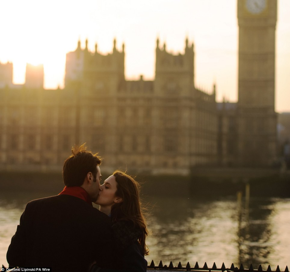 London love: A couple kiss by the Thames as the sun is setting behind the Houses of Parliament, in Westminster, central London