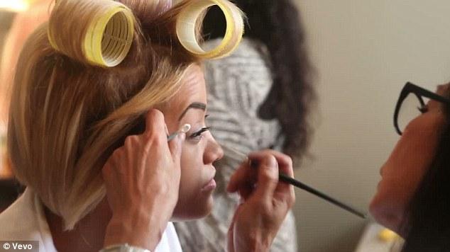 Preening: The singer wears huge rollers as she has her eye makeup applied