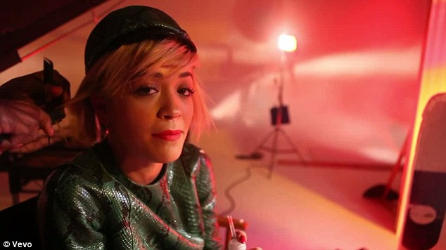 Star treatment: Rita holds still while her hair is preened for the video