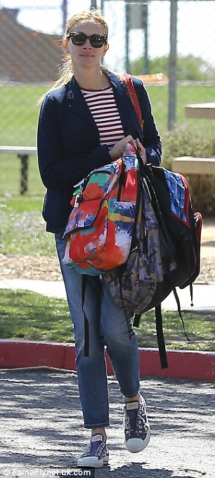 Busy mother: The Pretty Woman actress seemed to have her hands full as she carried three brightly coloured backpacks, presumably belonging to her children