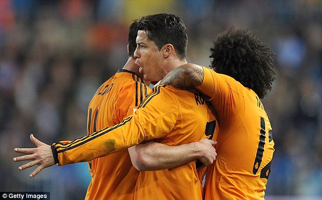 Man in the middle: Ronaldo celebrates with Marcelo (right) and Xabi Alonso (left)