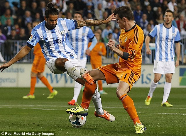 Down: Gareth Bale (right) is fouled by Marcos Angeleri of Malaga during the La Liga match