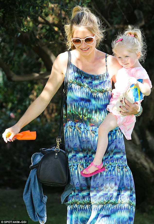 Mommy and me: The blonde beauty was all smiles as she juggled between her daughter and a purse full of belongings