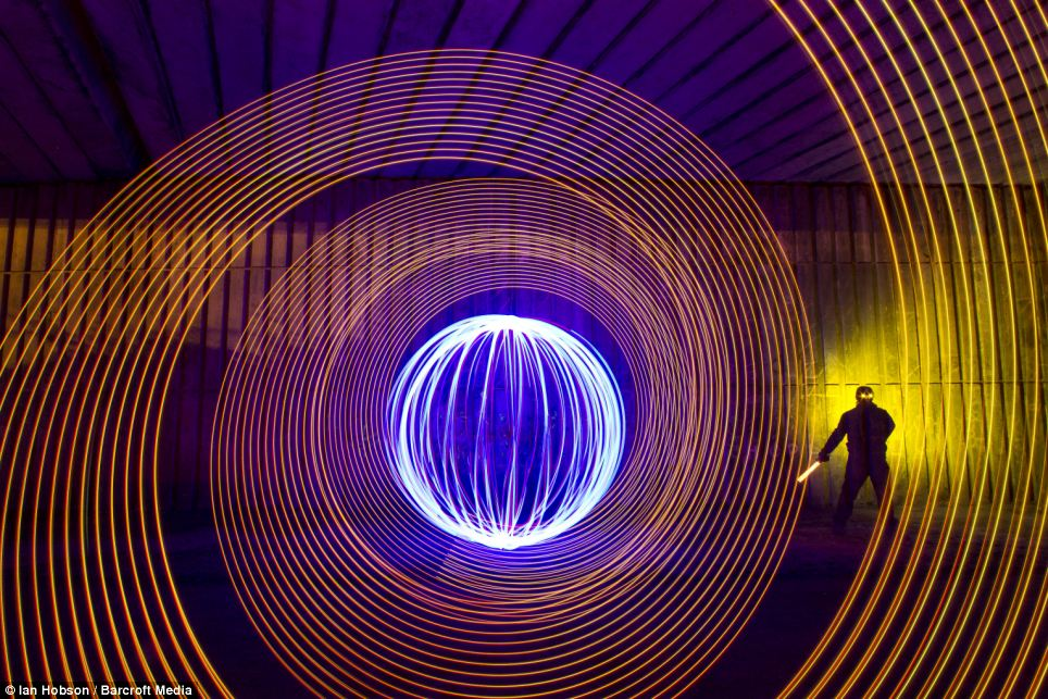 A work entitled 'Middle engine orb and self' by light artist Ian Hobson, made using LEDs spun on a wire, handheld LED strip with off camera flash and LEDs mounted on sunglasses, in a pedestrian underpass below a dual carriageway