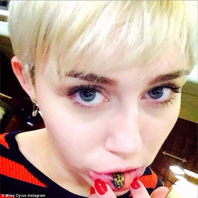New ink: Pop's latest wild child recently showed off a new crying cat tattoo on the inside of her lip