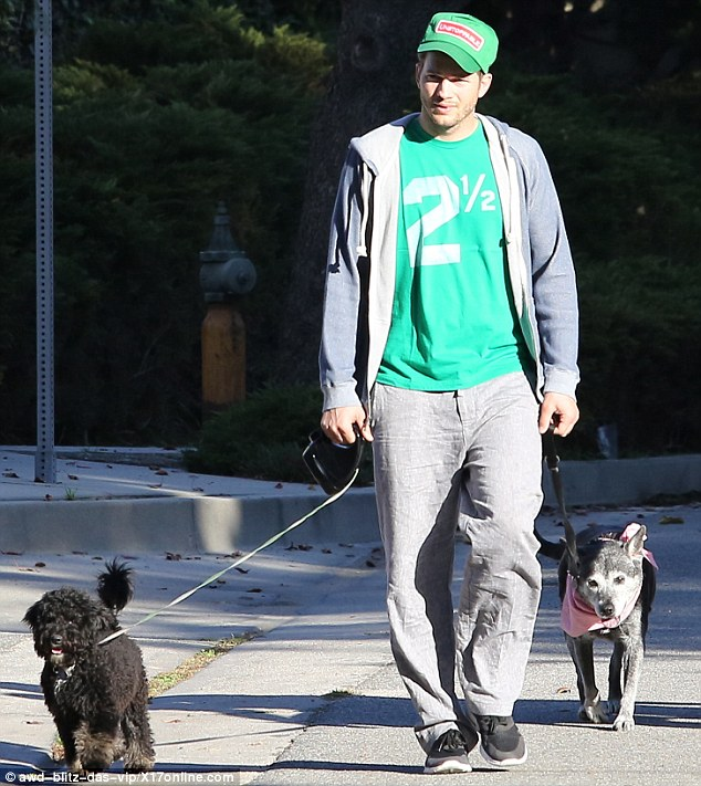 Luck of the Irish! Ashton Kutcher donned a green shirt and 'unstoppable' green hat in honour of St. Patrick's Day as he walked his pups in Los Angeles on Monday