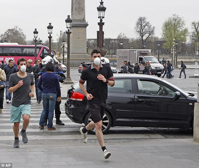 Two joggers wearing protective masks after pollution in Paris exceeded safe levels for five days in a row