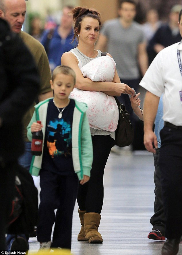 And back to reality: Britney was later spotted clutching a pillow at the airport heading back to Los Angeles after her sister's wedding on Sunday