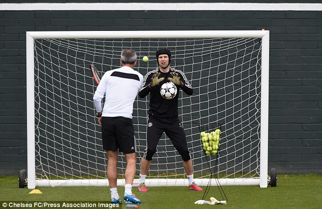Curious: Cech was put through his paces using a tennis racquet and tennis balls at Cobham