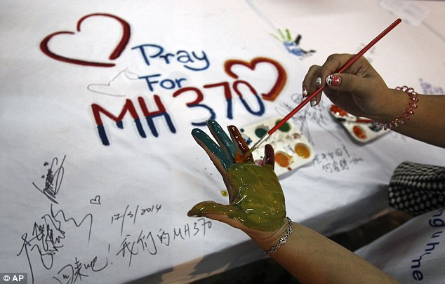 A woman paints her palm with water colors during an event for passengers aboard a missing Malaysia Airlines plane, in Kuala Lumpur, Malaysia. Authorities now believe someone on board the Boeing 777 shut down part of the aircraft's messaging system about the same time the plane with 239 people on board disappeared from civilian radar