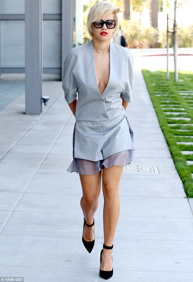 Get the Rita look! Ms Ora showed off her enviable figure in a plunging romper as she arrived at the Live Nation studios on Monday