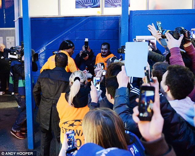 A warm welcome: Drogba is mobbed by fans and members of the media as he makes his way into Stamford Bridge