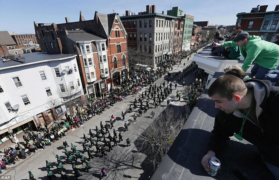 The view from above: Onlookers peer down from the rooftops as the St Patrick's Day parade makes its way through Boston