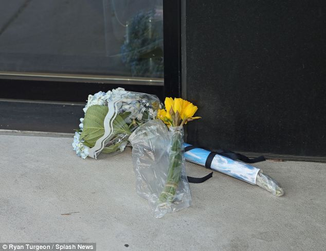 Flowers are left outside L'Wren Scott's apartment in New York where her body was discovered yesterday