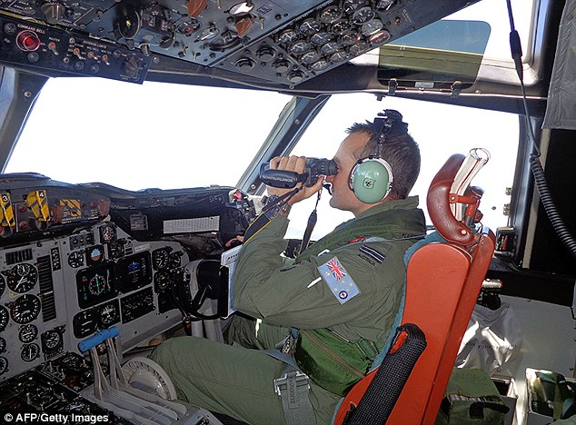 A Royal Australia Air Force pilot in an AP-3C Orion maritime patrol aircraft scans the surface of the sea during a search operation for the missing Malaysia Airlines Flight MH370 to the west of Peninsula Malaysia
