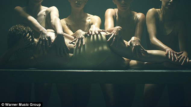 All hands on deck: Kylie is mauled by a number of bodysuit-clad women as she reclines on a table